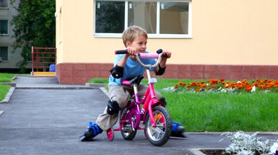 stock-footage-little-boy-in-elbow-pads-and-knee-pads-rollerblading-with-bicycle-outdoor